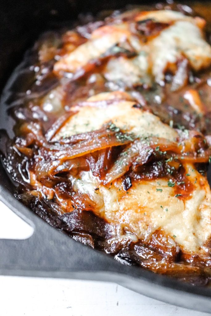 french onion chicken in a cast iron skillet up close on one chicken breast