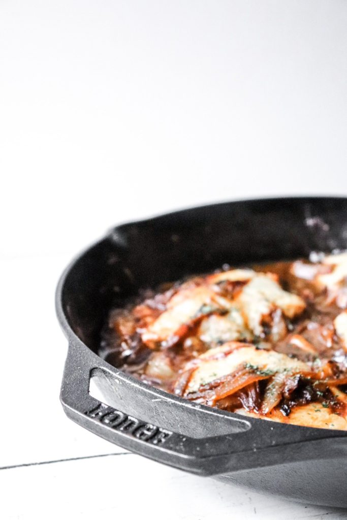 onion chicken side shot with lodge logo visible on the cast iron skillet