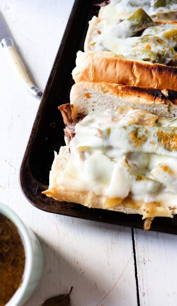 two completed beef sandwiches on a dark baking sheet with a knife and cup of au jus to the side