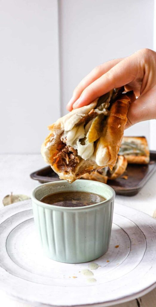 hand holding a beef sandwich that has a bite taken out of it and is being dipped into a ramekin of au jus.