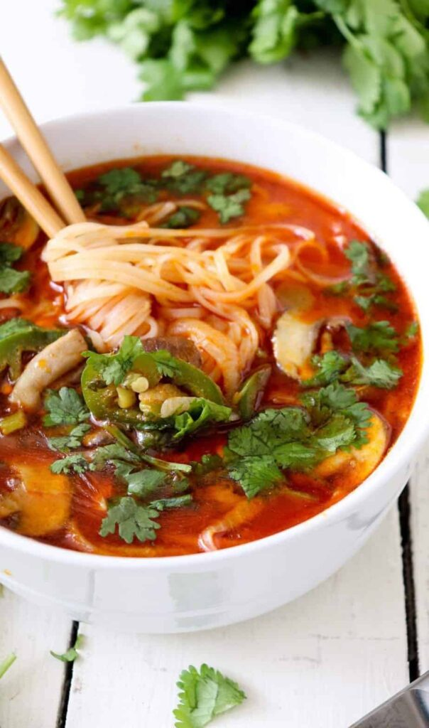 close up shot of thai noodle soup with chopsticks coming out of the bowl