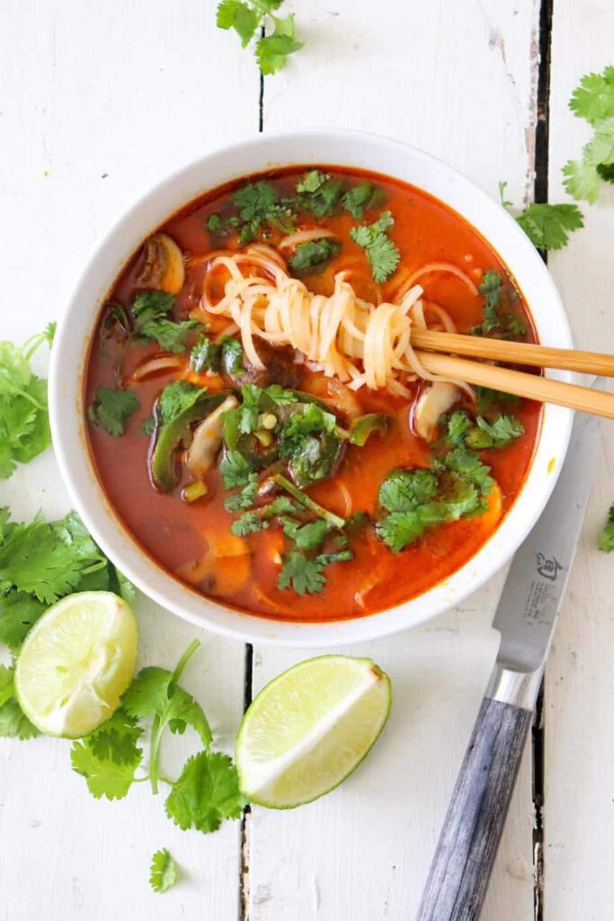 overhead shot of red curry soup with limes and cilantro sprinkled around