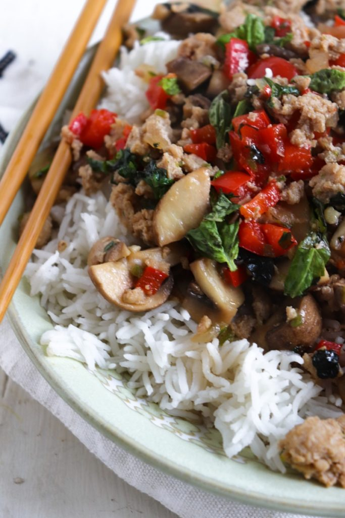 spicy basil chicken on rice with chopsticks close up