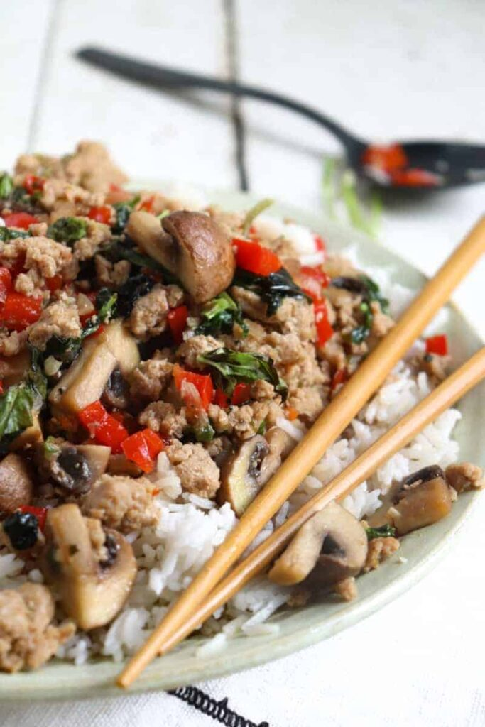 pad kra pao over rice in a flat green bowl
