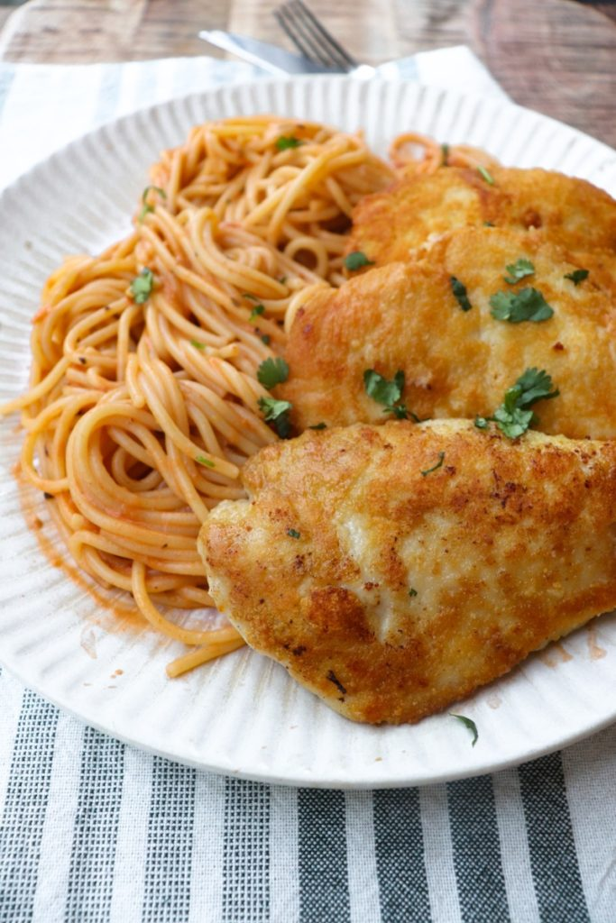 chicken on a white plate with spaghetti  and a green and white striped napkin