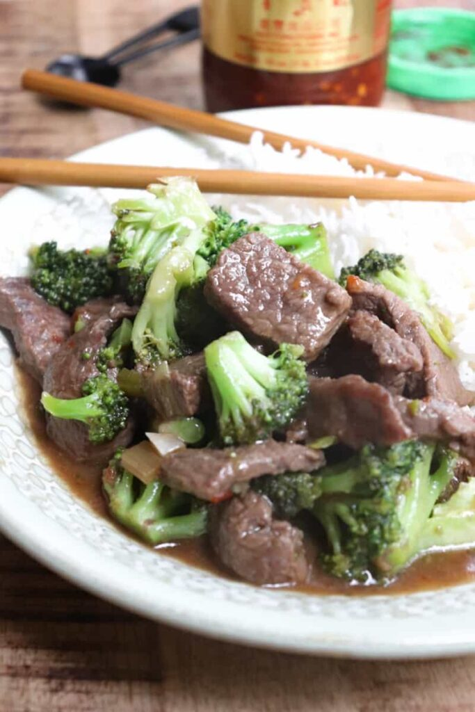 beef and broccoli florets with a brown sauce, plated with rice on a green bowl with chopsticks