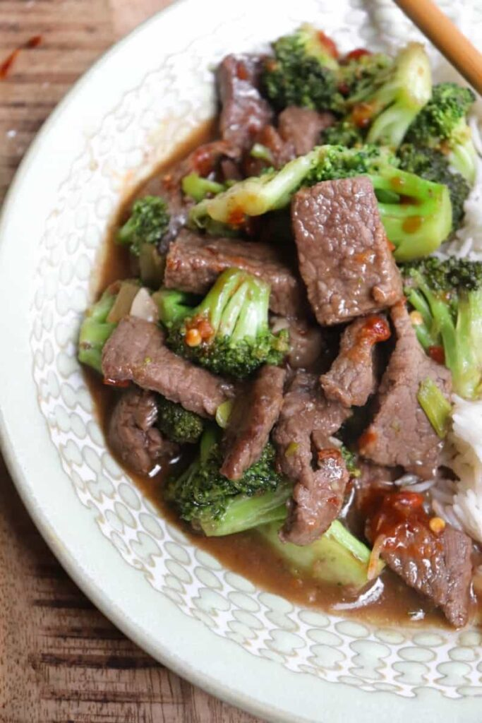 sirloin steak cut into small pieces with broccoli florets in a brown sauce on a green plate