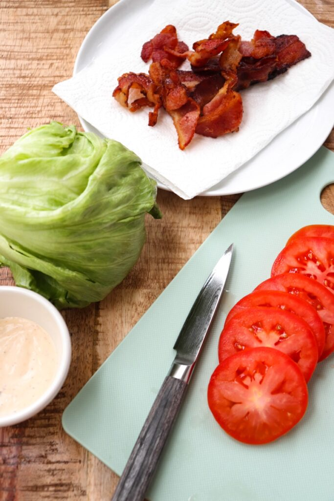 tomatoes sliced on a mint green cutting board with a knife next to it, ranch in a small white bowl, iceberg lettuce, and bacon on a paper towel on a white plate