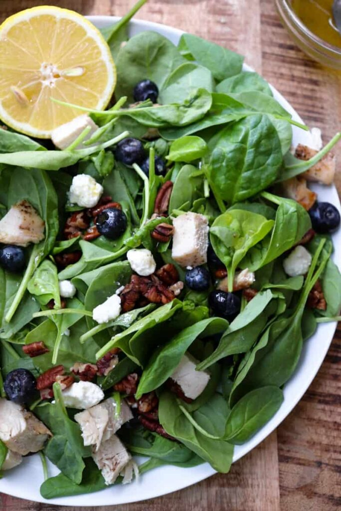 close up of blueberry spinach salad with a lemon wedge in the corner of the plate.