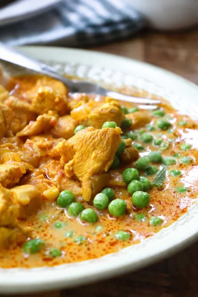 butter chicken with green peas in gravy on a green plate with a fork in the sauce with a striped towel in the background