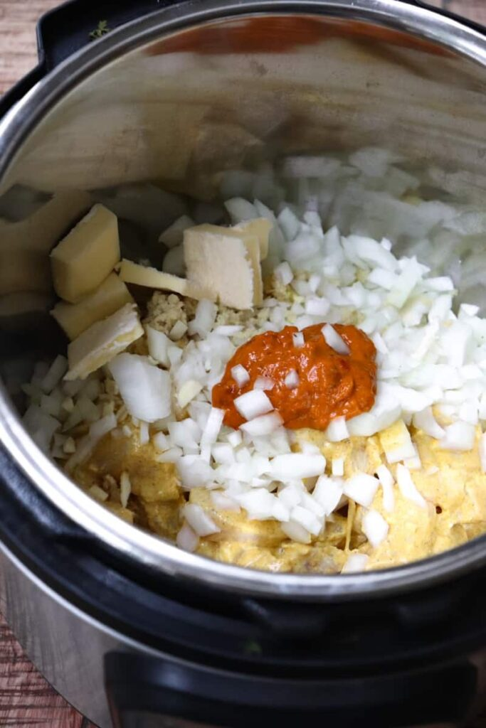 uncooked butter chicken ingredients in the instant pot. Most visible is onion, butter, and curry paste.
