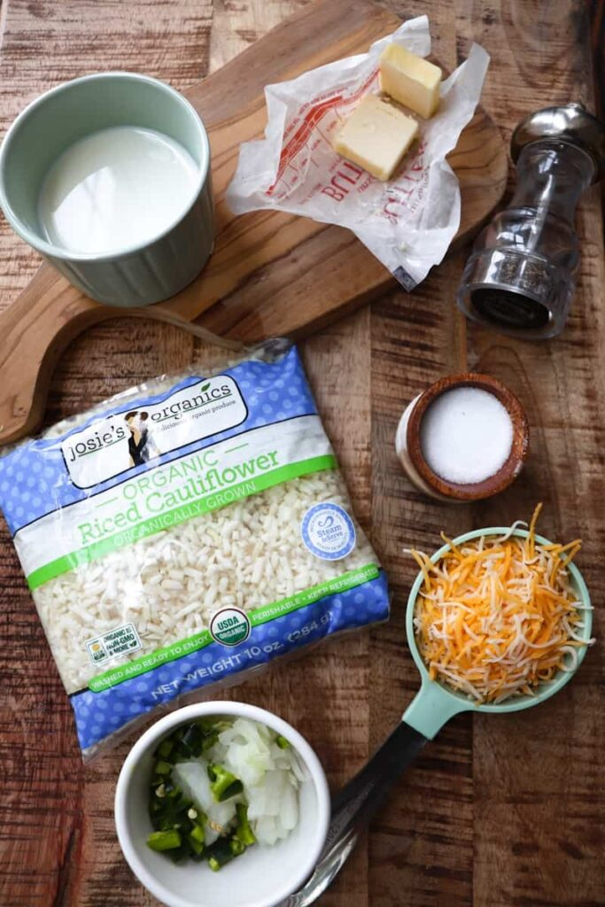ingredients for cheesy rice laid out with a wooden cutting board