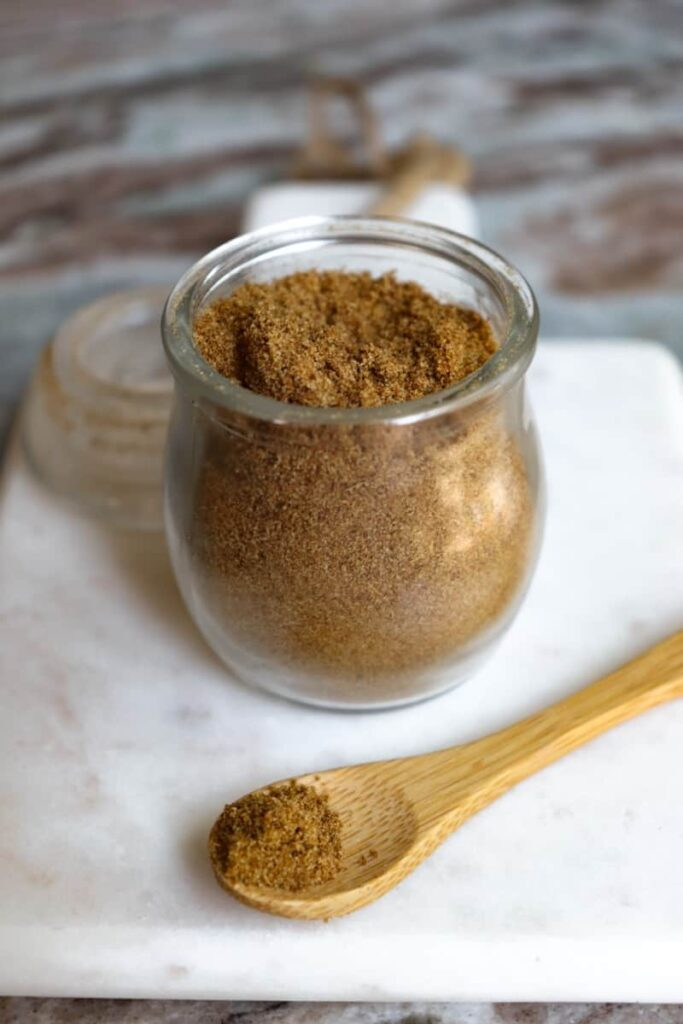 ground cumin in a glass jar with a wooden spoon placed at an angle in front on a white marble cutting board
