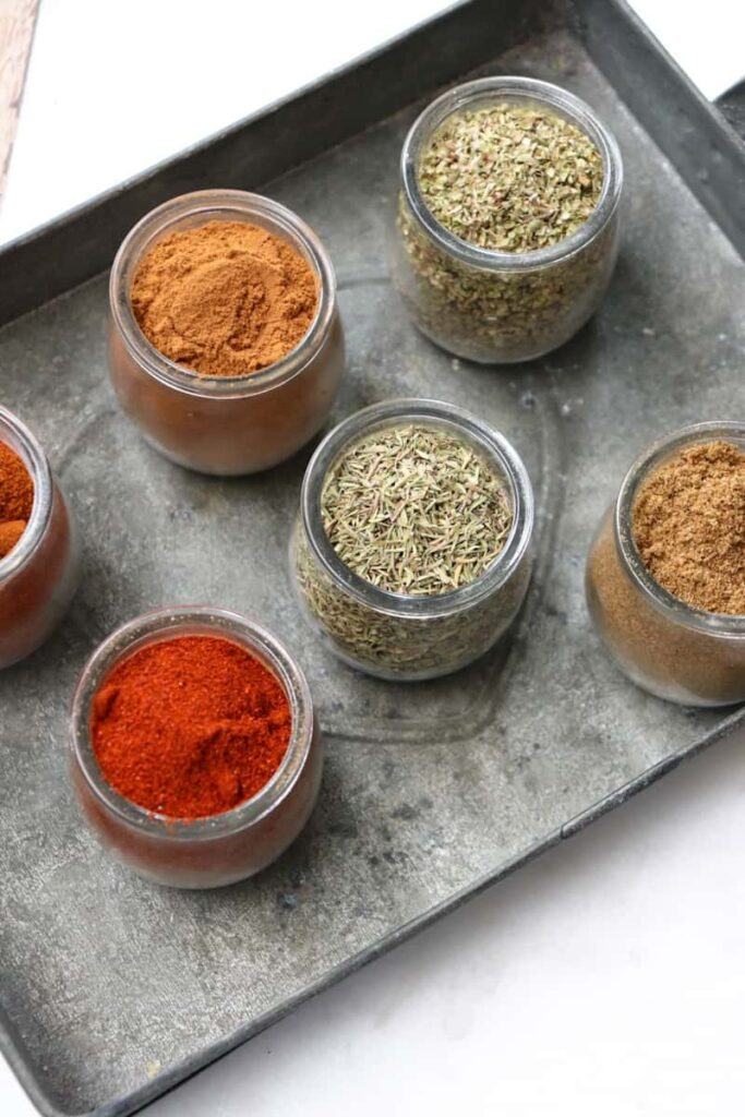 six classic spices in glass jars on a metal dish