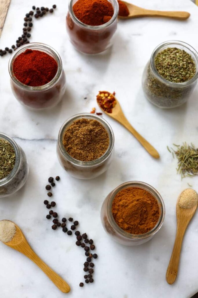 essential spices in glass jars placed decoratively on a white marble slab