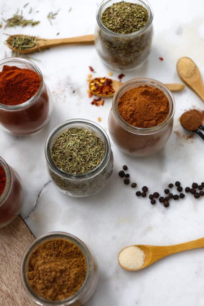 kitchen spices and herbs in glass jars and on wooden spoons placed decoratively on a whtie marble slab