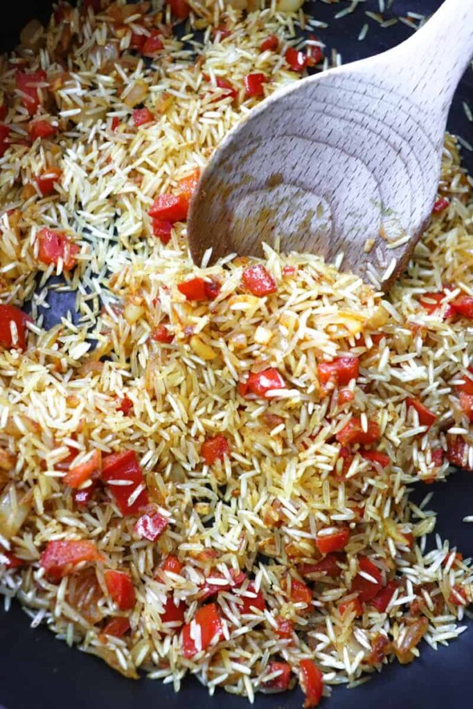 dry rice, diced peppers and onions, and spices in a dark grey pan with a wooden spoon coming out