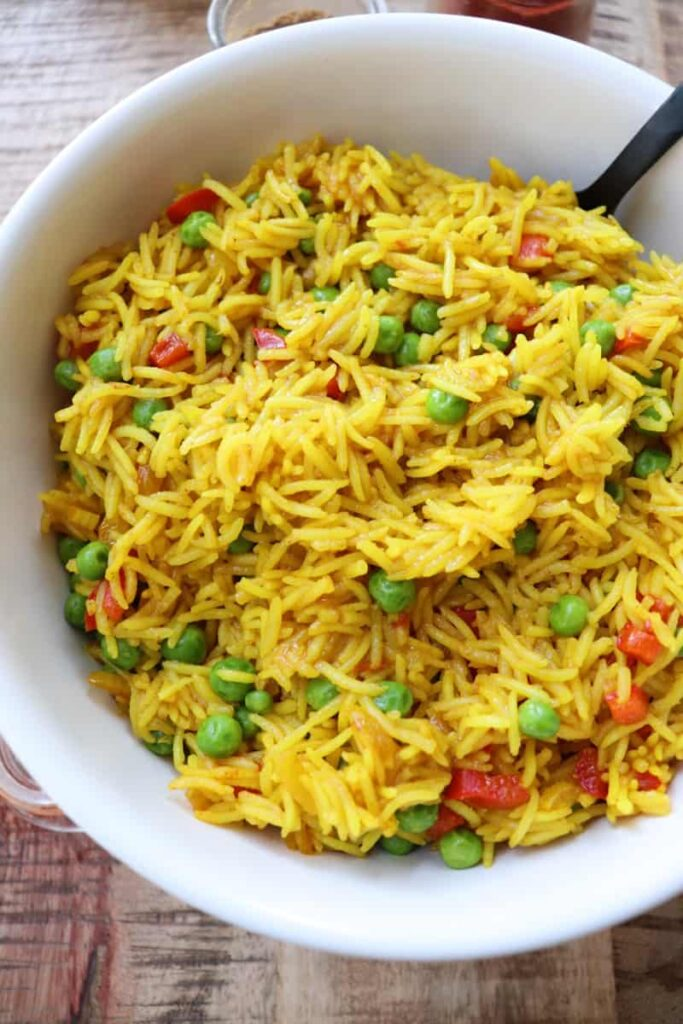yellow rice in a white bowl with peas and diced red pepper. two spice jars open on the wooden background