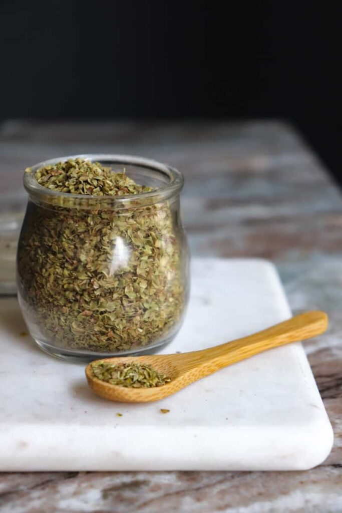 dried oregano in a glass jar with a wooden spoon placed at an angle in front on a white marble cutting board