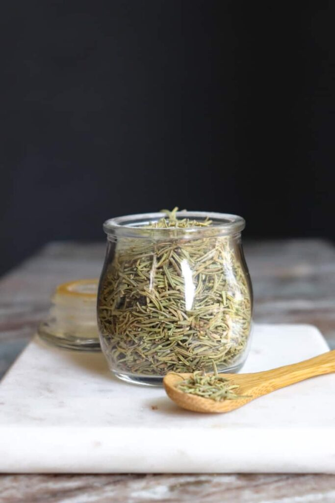 dried rosemary in a glass jar with a wooden spoon placed at an angle in front on a white marble cutting board