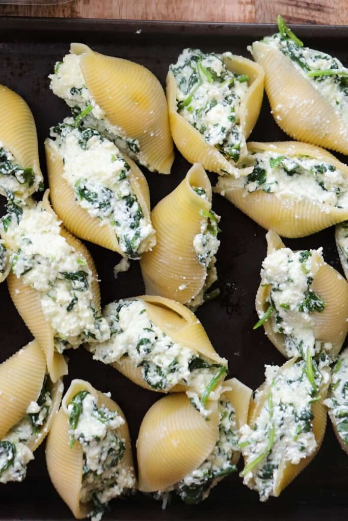 uncooked shells filled with  cheese mixture on a dark sheet pan