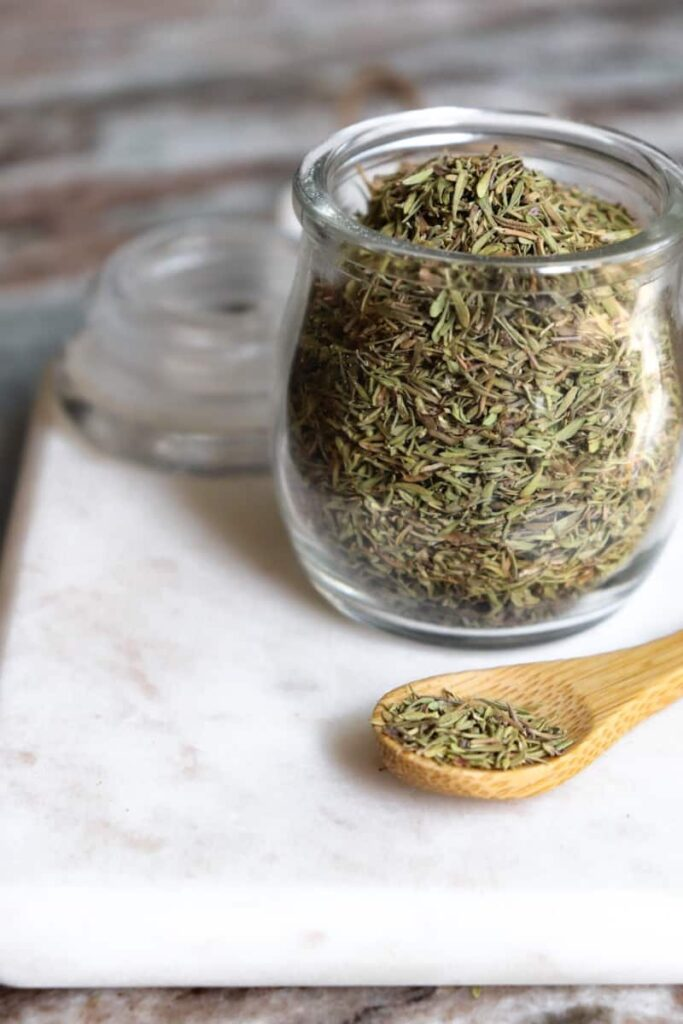 dried thyme in a glass jar with a wooden spoon placed at an angle in front on a white marble cutting board