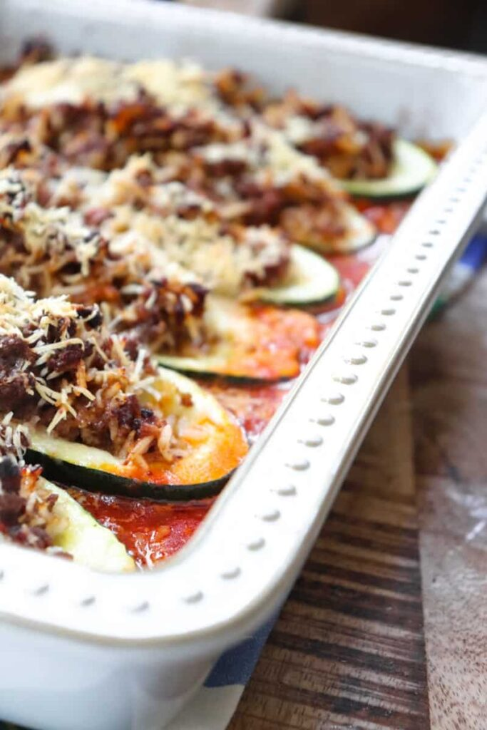 angled shot of baked zucchini in a cream colored casserole dish