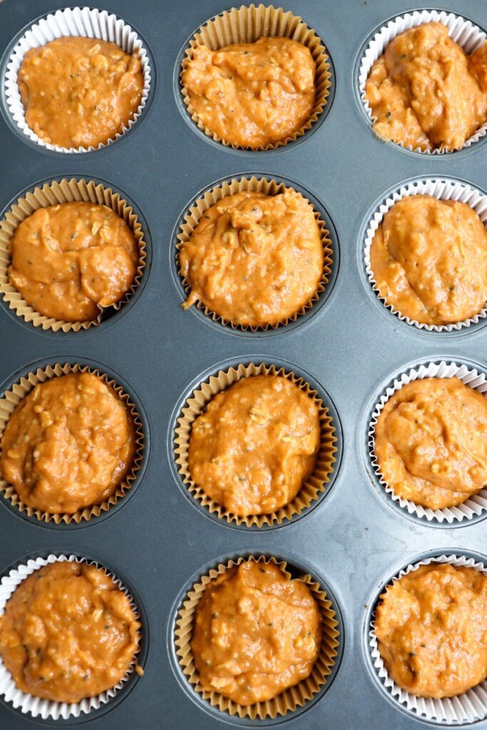 overhead shot of pumpkin muffin batter in various color liners in a muffin tin