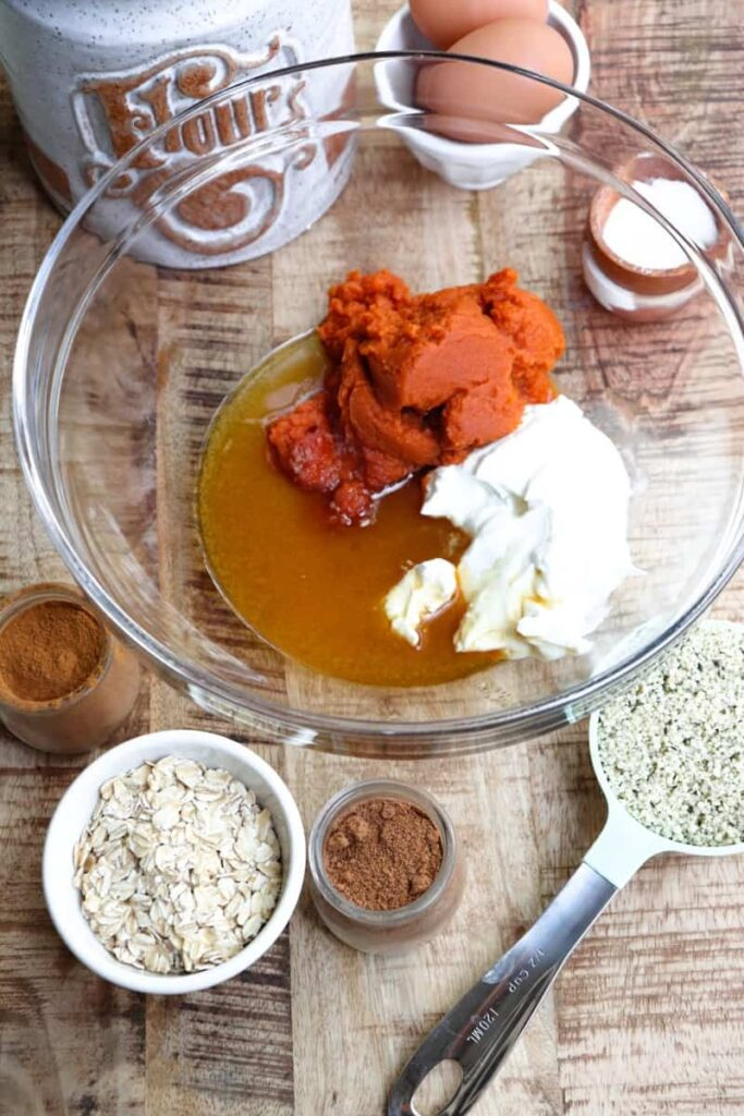 protein pumpkin muffins ingredients in small bowls and measuring spoons