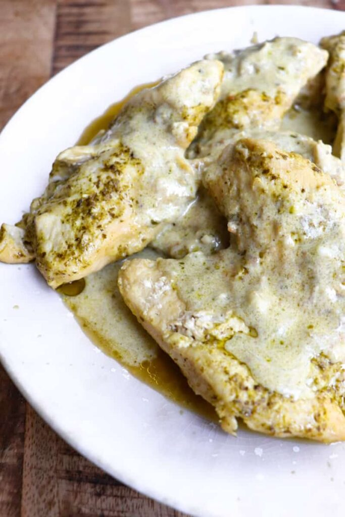 cooked chicken covered in creamy pesto sauce on a white plate