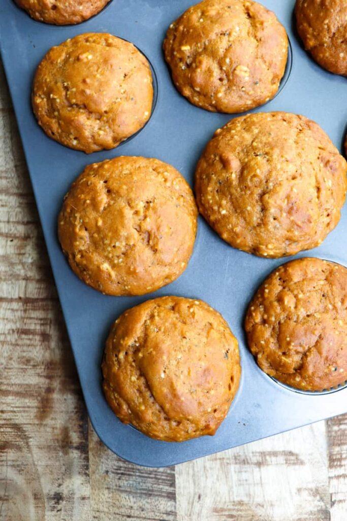 baked pumpkin muffins in dark gray muffin tin