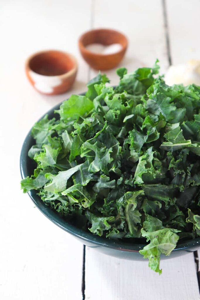 chopped kale in a green bowl with two mini wooden bowls in the background