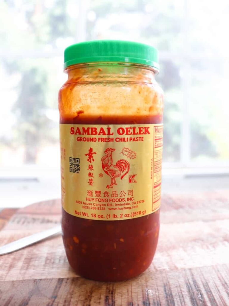 jar of sambal oelek with a green lid in front of a window