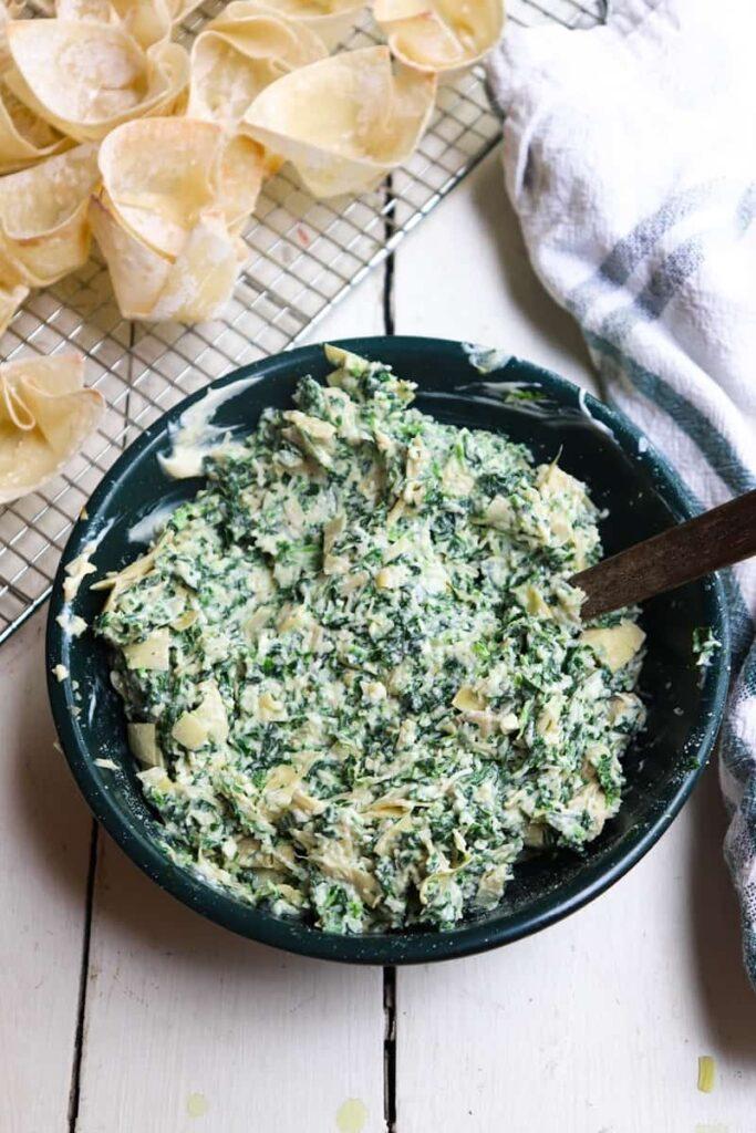 spinach artichoke dip in a green bowl