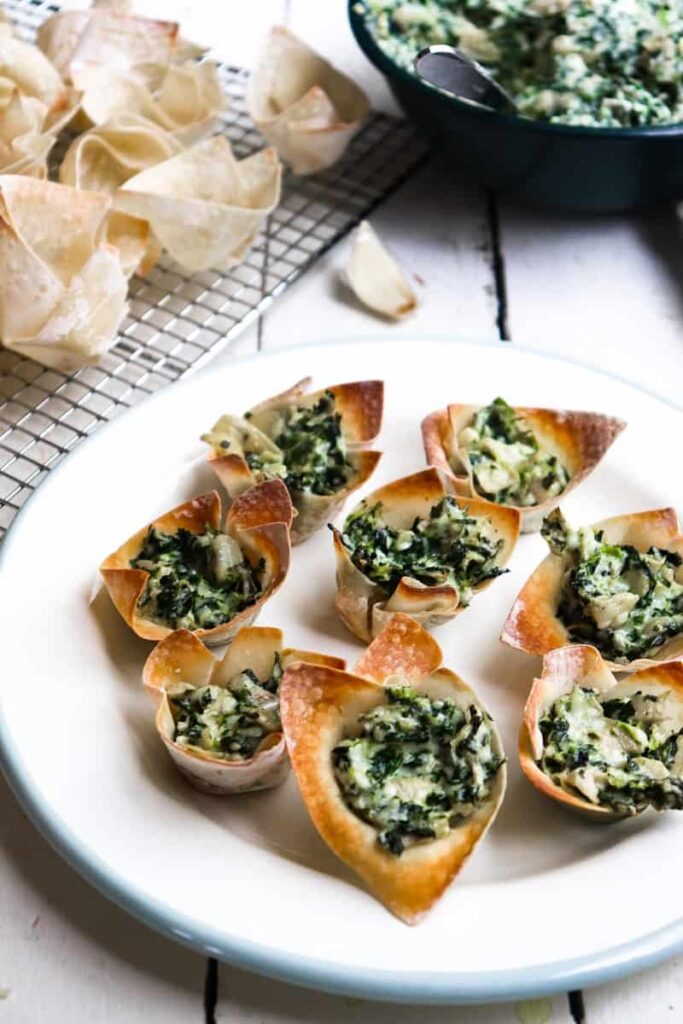 completed spinach bites on a white plated with the ingredients in the background