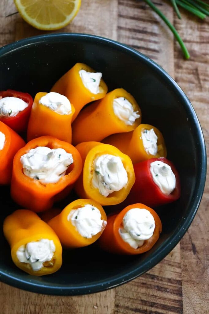 stuffed mini peppers with cream cheese filling in a dark green bowl