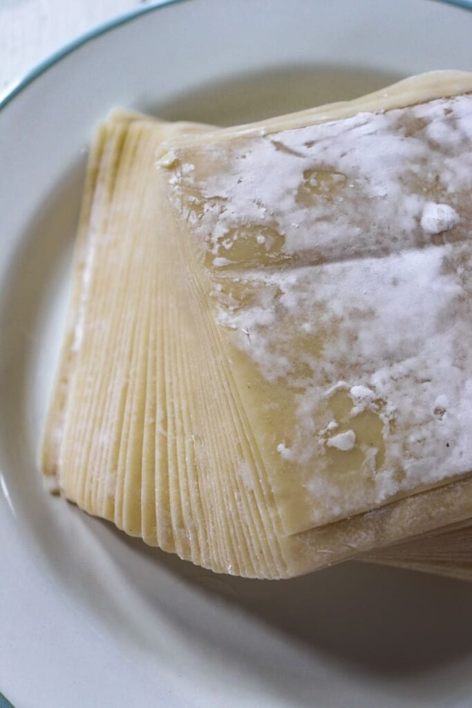 a stack on raw wonton wrappers on a white plate