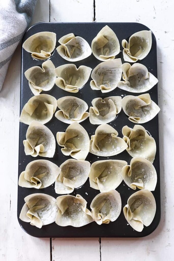wonton wrappers placed in a mini cupcake tin